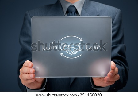Win-win partnership strategy concept. Businessman with drawn win-win scheme and handshake partnership agreement on futuristic tablet computer.