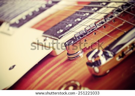 close up of an electric guitar bridge in vintage effect #251221033
