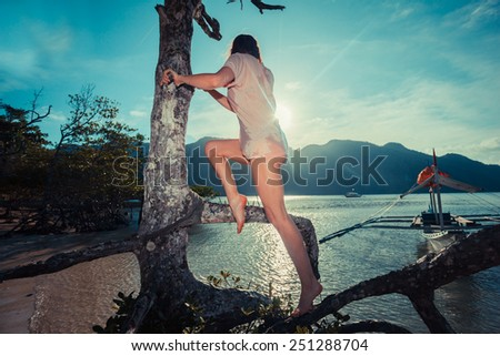 A young woman is climbing a tree on a tropical beach #251288704