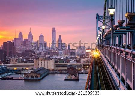 Philadelphia under a hazy purple sunset. An incoming train crosses Ben Franklin Bridge.