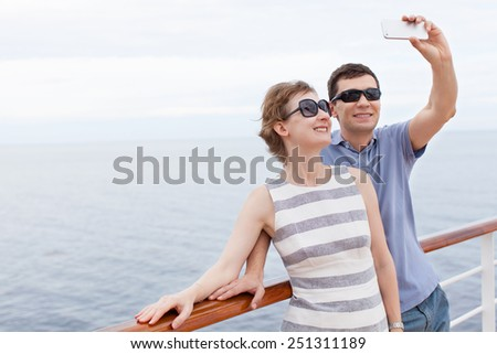 young couple taking selfie with smartphone while cruising, vacation concept