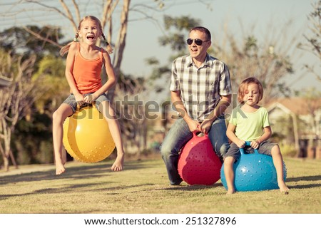Dad and children playing on the lawn in front of house at the day time #251327896