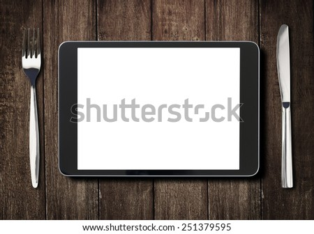black tablet pc or ipad on dark wooden table with fork and knife