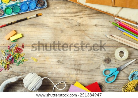 Desk of an artist with lots of stationery objects. Studio shot on wooden background. Royalty-Free Stock Photo #251384947