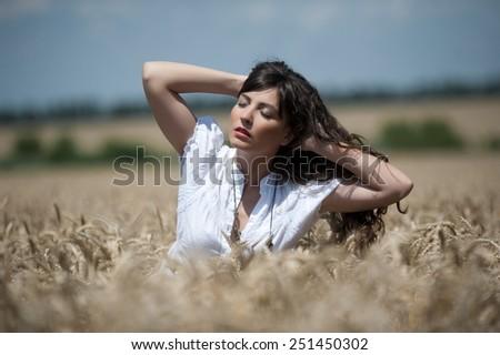 Beautiful sexy brunette girl posing in a wheat field #251450302