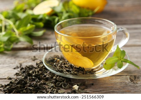 Cup with green tea on grey wooden background Royalty-Free Stock Photo #251566309