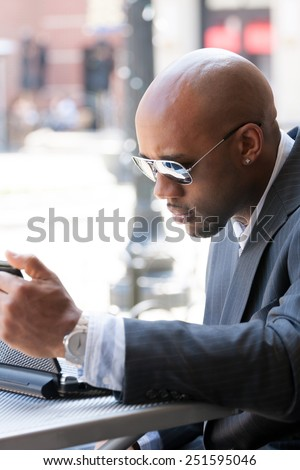 A business man in his early 30s working on his laptop or netbook computer outdoors. #251595046