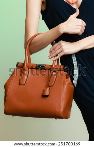 Elegant outfit. Stylish woman fashionable girl with brown leather handbag bag on green. Fashion and female beauty. #251700169