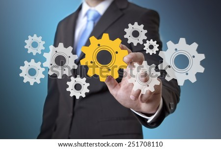 Businessman playing with gears and various cogwheels #251708110