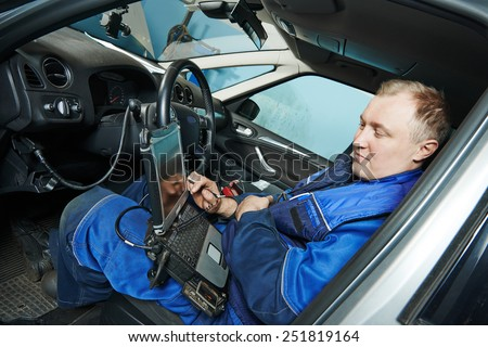 automobile computer diagnosis auto repairman industry mechanic worker servicing car auto in repair or maintenance shop service station #251819164