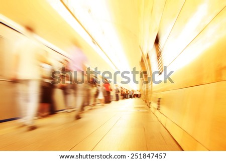 Motion blurred commuters walking in subway station. #251847457