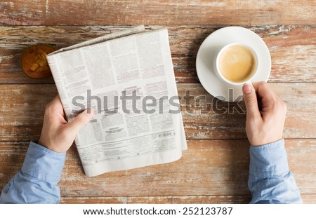 business, information, people and mass media concept - close up of male hands with newspaper, muffin and coffee cup on table Royalty-Free Stock Photo #252123787