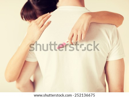 close up of woman with pregnancy test hugging man #252136675