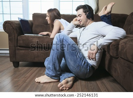 A woman lay on the sofa with laptop and a man ear music #252146131