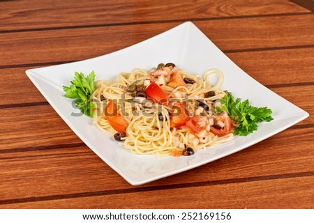Pasta with tomato, black olives, capers and greens #252169156