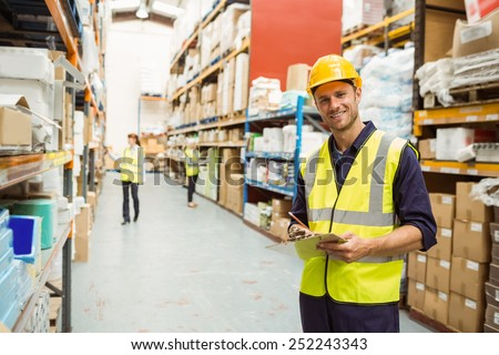 Warehouse worker smiling at camera with clipboard in a large warehouse #252243343