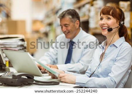 Warehouse manager working at her desk wearing headset in a large warehouse #252244240