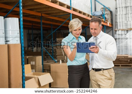 Warehouse managers looking at tablet pc in a large warehouse #252244246
