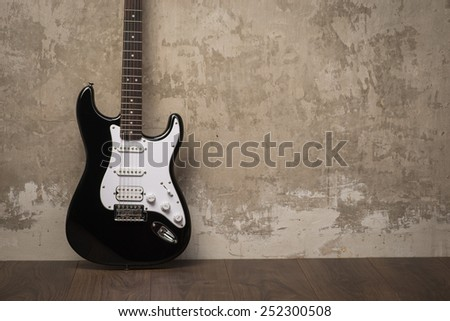 Black and white guitar on the floor near the concrete wall