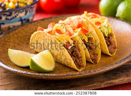 A plate of delicious tacos with lime, tomato, lettuce, and cheese.