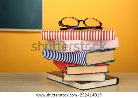 Stack of books with glasses on wooden desk, on colorful wall and blackboard background #252414019