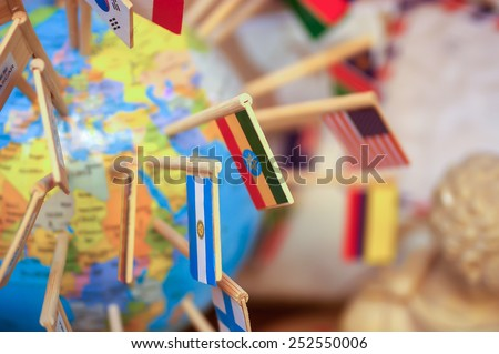Close-up national flags stuck in the globe