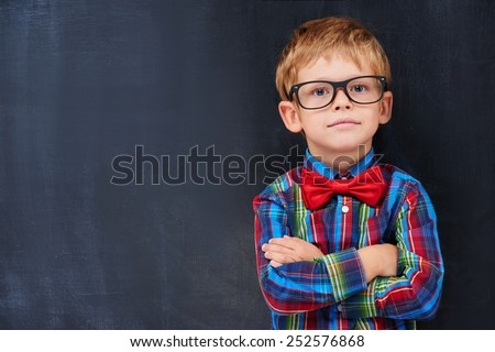 Cute ginger boy standing against blackboard background