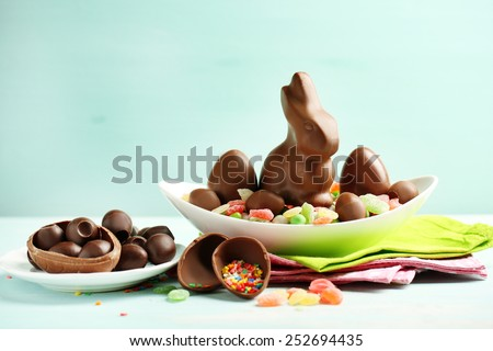 Chocolate Easter eggs and rabbit on plate, on color wooden background Royalty-Free Stock Photo #252694435
