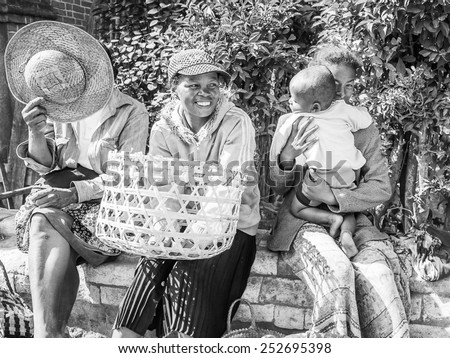 ANTANANARIVO, MADAGASCAR - JUNE 30, 2011: Unidentified Madagascar women sell apples and other fruits at the market. People in Madagascar suffer of poverty due to the slow development of the country #252695398