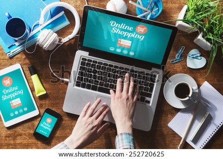Online shopping website on laptop screen with female hands typing Royalty-Free Stock Photo #252720625
