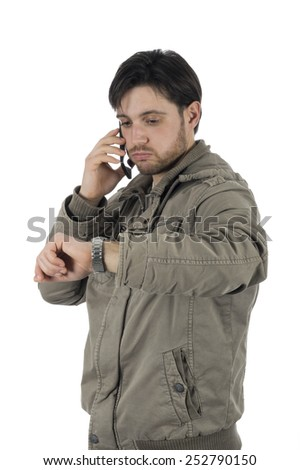 Young busy man looking at the time on his wrist watch while talking on mobile #252790150