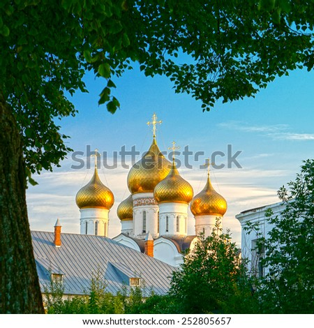 Ancient Russian church shining golden domes in the setting sun against the blue sky framed by green leaves #252805657