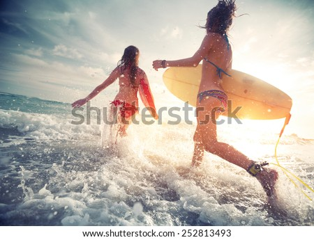 Two young ladies surfers running into the sea with surf boards Royalty-Free Stock Photo #252813493