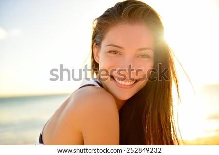 Asian beautiful girl smiling happy on beach vacation enjoying warm sunshine. Mixed race Asian Caucasian pretty model outside with sun in background on Hawaiian tropical beach. #252849232