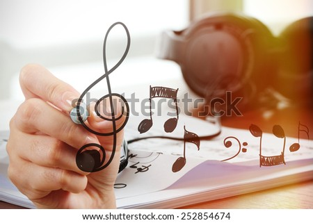 close up of Hand drawing musical notes on screen as music composer concept