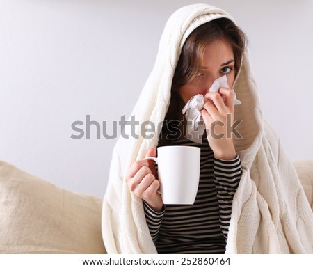 Sick woman covered with blanket holding cup of tea sitting on sofa couch #252860464