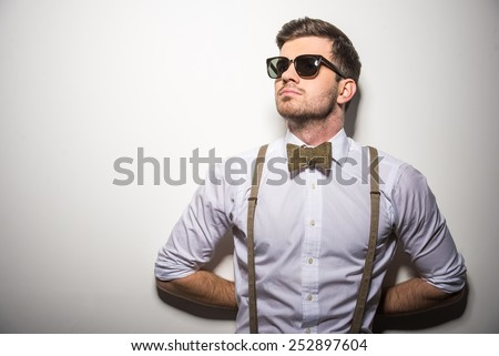 Portrait of young trendy man with black glasses, suspenders and bow-tie on gray background. #252897604