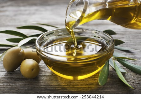 Bottle pouring virgin olive oil in a bowl close up #253044214