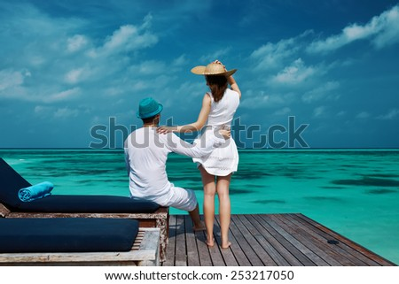 Couple on a tropical beach jetty at Maldives #253217050