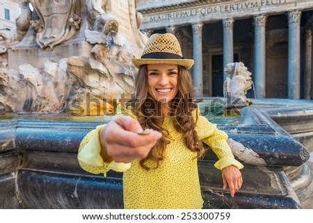 Young woman tossing coin near fountain of the pantheon in rome, italy #253300759