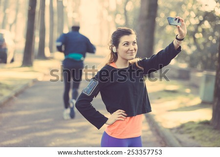 Young Sporty Woman Taking a Selfie at Park. She is Looking at Smart Phone, Wearing a Black Sweatshirt. She has a Smart Phone Holder on her Arm and Listen Music with Earphones.