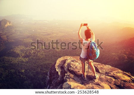 woman hiker taking photo with smart phone at mountain peak cliff