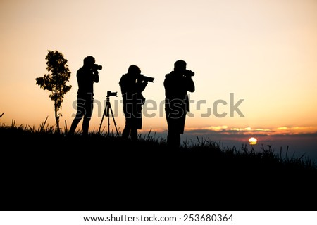 silouette man taking photo of sun rise #253680364