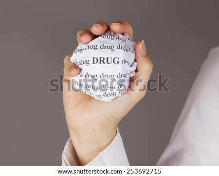 """Crumpled paper ball with words """"Drug"""" in woman hand on grey background #253692715"""