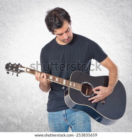 Handsome man with guitar over textured background #253835659