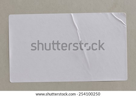Stickers Label Close Up on Cardboard Background with Real Shadow. Top View of Adhesive Paper Tag. Copy Space for Text or Image #254100250