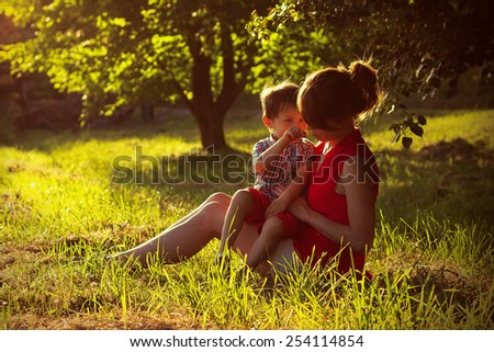 Little boy and his mother are sitting in a forest meadow  #254114854