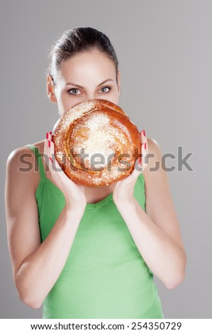 Attractive girl looks out behind a round bun, over gray background. #254350729