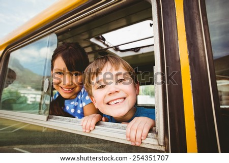 Cute pupils smiling at camera in the school bus outside the elementary school #254351707