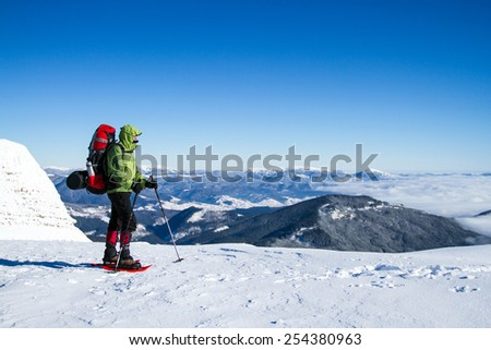 Winter hiking in the mountains on snowshoes with a backpack and tent. #254380963